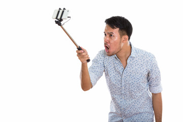 Young angry Asian man taking selfie picture with mobile phone wh