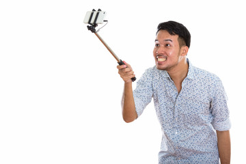 Young happy Asian man smiling and taking selfie picture with mob