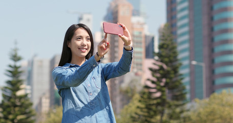 Woman taking photo with cellphone in city