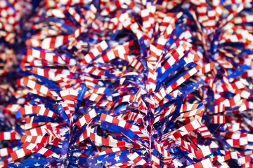 Red white and blue stars and stripes tinsel - selective focus on front with blurred bokeh - festive patriotic background