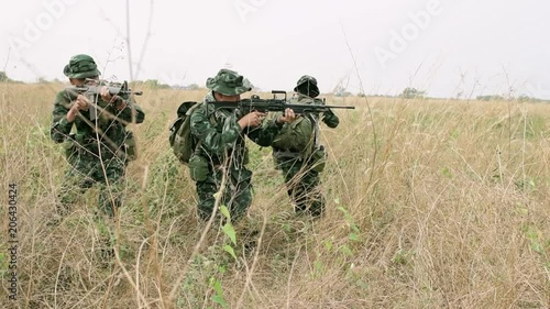 Slow Motion Of Soldiers Aiming Their Assault Rifles On Grass