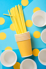 Yellow straws for a party in paper cups on a bright background