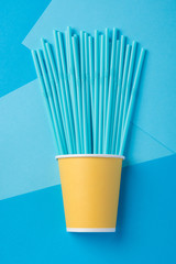 Blue straws for a party in paper cups on a bright background