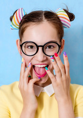 A young beautiful girl with a funny hairstyle wearing glasses is holding hands with a bright manicure near her face, laughing, rejoicing. A vivid image.