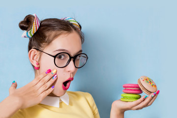 A young beautiful girl with glasses is holding a multicolored macaroons in her hand and is surprised. Hand with bright manicure on cheek, funny hair.