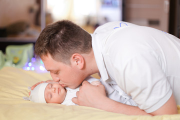 Young caucasian father holding and kissing newborn baby. Concept of newborns and parents.