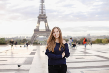 Pretty woman standing in Eiffel Tower background in Paris. Concept of famous landmarks in France and tourism.