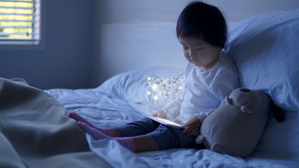 Small Asian chinese toddler sitting on the bed with special effects from ipad