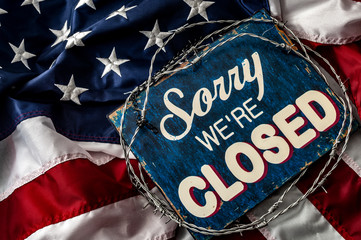 Political isolationism and economic slowdown in the United States of America concept with close up a sorry we're closed sign wrapped in barbwire on top of the american flag