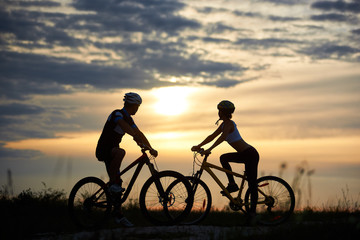 A man and a woman on bicycles stand on the road among the field grass opposite each other and look to the side at sunset. A magical sky with clouds among which the sun that sits is seen