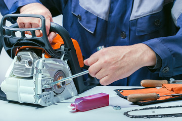 Professional technician working in repair service. Repairing chainsaw on workbench.