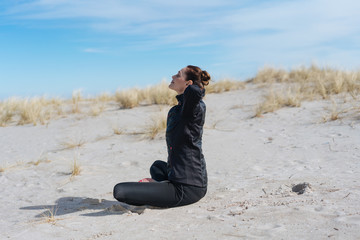 Young woman meditating in the sun at the beach