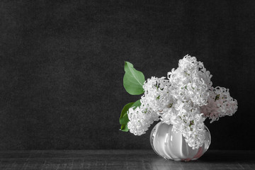 Fresh bouquet of white lilac flowers in the vase on dark background. Condolence card. Empty place for emotional, sentimental text or quote.