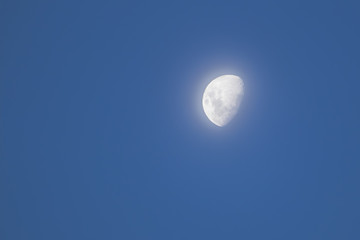 Day time half  moon with smooth light behind