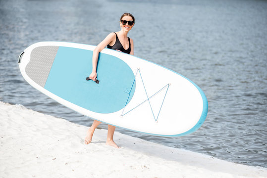 Young woman in black swimsuit standing with standup paddleboard on the beach ready for surfing