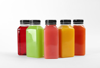 Bottles with delicious colorful juices on white background