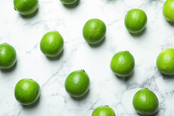 Fresh ripe green limes on marble background