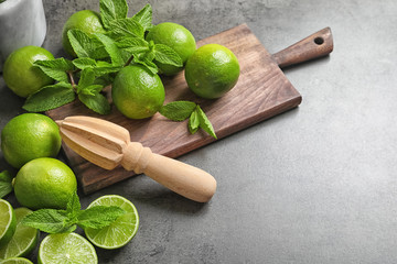 Composition with ripe limes, mint and juicer on grey background. Refreshing beverage recipe
