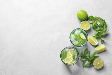 Flat lay composition with refreshing lime beverage and ingredients on light background
