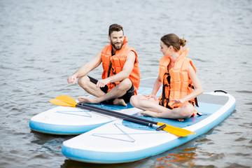 Couple in life vest relaxing on the stand up paddle board doing yoga