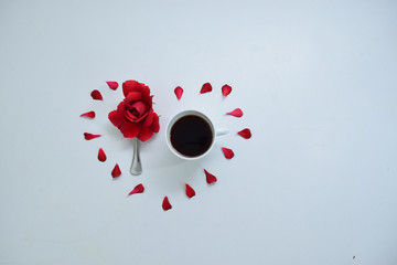 cup of coffee and a red rose in a heart made with red petals