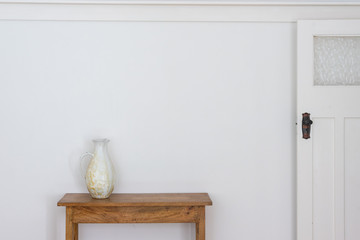 White jug on wooden side table against wall with retro doorf
