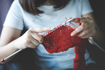 Close up shot of young woman hands knitting a red scarf handicraft in the living room on terrace at home