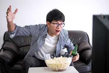 Young Asian Man fanclub watching soccer match on tv and cheering football team, celebrating with beer and popcorn at home, sports and entertainment concept