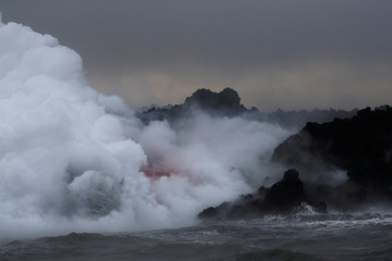 Lava glows through the laze as it pours into the ocean during the eruption of the Kilauea Volcano near Pahoa, Hawaii