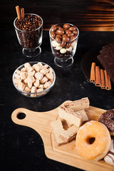 Donuts, peanuts in chocolate and coffee beans on wooden background
