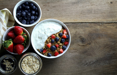 Healthy breakfast, Bowl of yogurt with granola and Fresh fruit on Wood background