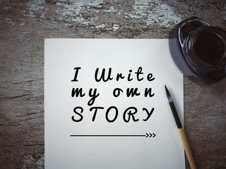 Motivational and inspirational quote - 'I write my own story' written on a white piece of paper. With vintage styled background.