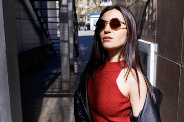 A large portrait of a young beautiful girl with glasses and a leather jacket. Urban style of the street. Cold season. Fashionable portrait. Sunglasses, glasses