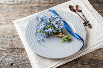 Forget me not flowers bouquet in grey plate on wooden background