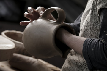 Professional female potter working with clay