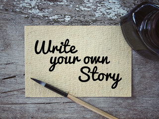 Motivational and inspirational quote - 'Write your own story' written on a white piece of paper. With vintage styled background.