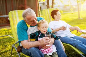 Elderly man sitting on a lazy chair outside holding his gorgeous smiling grandson and offering him water.