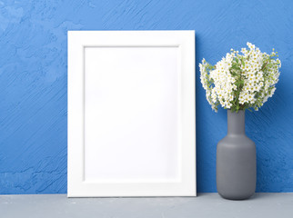 Blank white frame, flower in vaze on gray table against dark blue concrete wall with copy space. Mock up.
