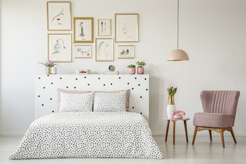 Dotted, double bed, paintings with gold frames and pink armchair set in a serene bedroom interior