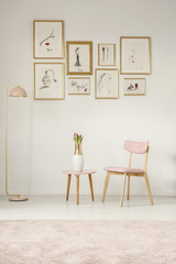Paintings in golden frames, pink chair, table and lamp set on the white wall in a sitting area