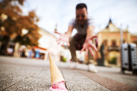 Close up picture of an icecream on street dropped by a mourning man.