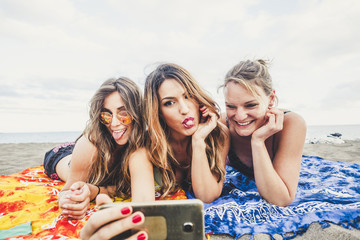 group of caucasian three women young  beautiful taking pictures with smartphone at the beach during vacation and outdoor activity. crazy and nice expression face for friendship and freedom concept
