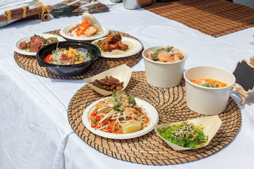 food samples, variations of diverse Asian dishes served on trays during the Asian street farmers market. Soft shell Crab Bao, roasted silkworm, Tom Yum Ramen,