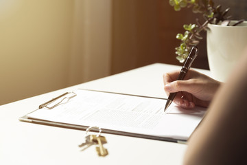 Woman signing a contract document making a real estate purchase deal