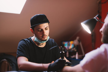 Young focused tattoo artist is inking customers arm carefully in his shop.