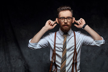 Young stylish hipster businessman or manager is stretching his ears, imitating monkey in a funny way or pretending not hearing somebody's words, information or other sounds