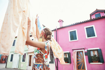 Young fashionable woman in romantic colorful dress and headband ,with big earring hanging clothes out near pink house in Burano island, Venice, Italy