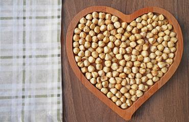 Hazelnut in heart-shaped wooden bowl on wooden table