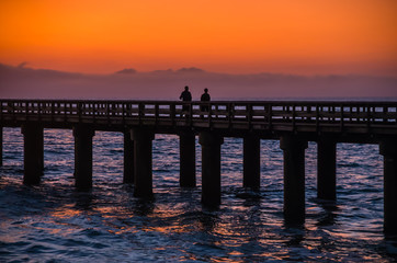Foto auf AluDibond Fantasie-Landschaft Silhouettes of two people walking on wooden pier at the ocean during amazing sunset, orange and purple sky