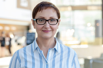 Closeup portrait of middle aged woman wearing glasses. Professional headshot of businesswoman, teacher, manager. Blurred office background.